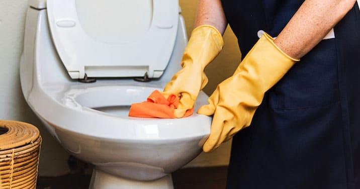 Employé de nos services d'entretien ménager commercial nettoyant les toilettes