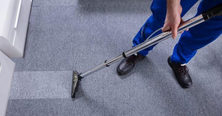 Employé de MOM nettoyage industriel nettoyant un tapis de bureau à Montréal