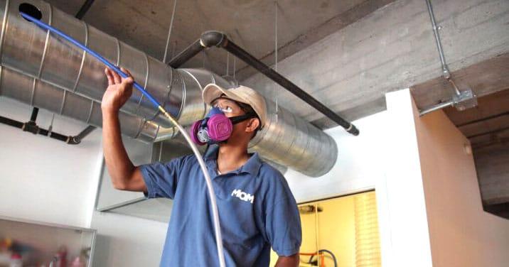 Employé de MOM nettoyage industriel nettoyant un conduit d'aération