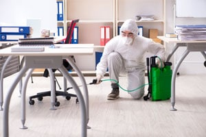 Employee in the process of disinfecting Covid19 in an office